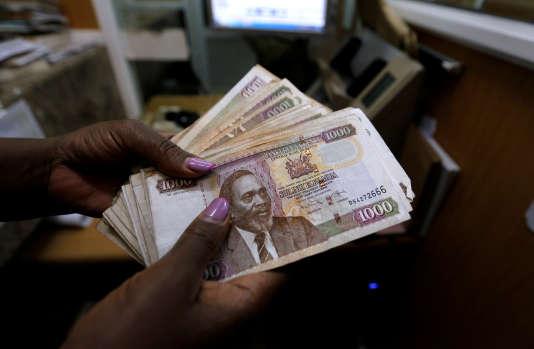 Une caissière compte des billets de shillings kényans dans un bureau de change à Nairobi, la capitale du Kenya, le 20 avril 2016.