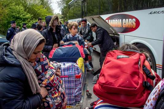 Des migrants du camp de Grande-Synthe montent dans l'un des bus qui les conduira dans un centre d'accueil et d'orientation, le 14 avril.