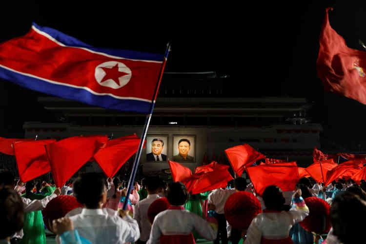 Dans la nuit de samedi à dimanche, des habitants de Pyongyang rassemblés sous les portraits illuminés de Kim Il-sung et Kim Jong-il.