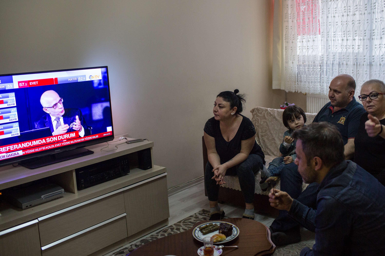 La famille Ulker suit les résultats et les débats à la télévision dans sa maison située dans le quartier de Kasimpasa, à Istanbul, dimanche 16 avril.