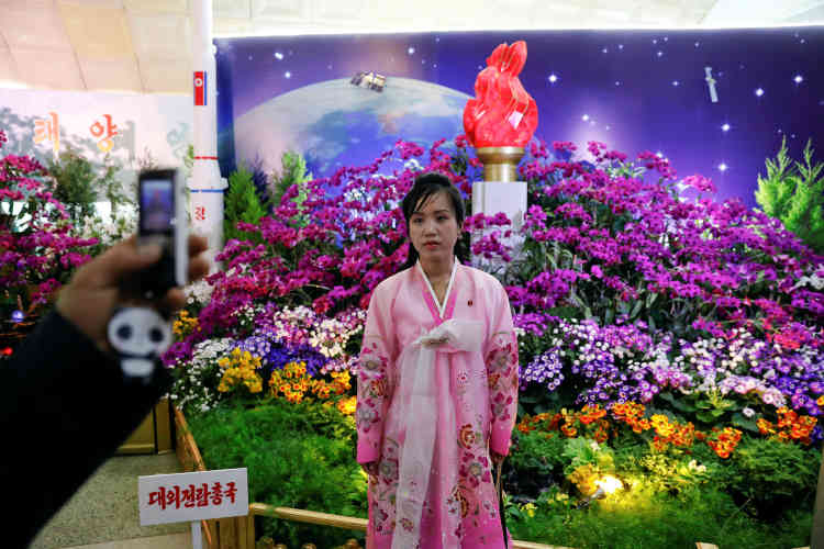 Une habitante de Pyongyang en costume traditionnel pose devant un parterre de fleurs.