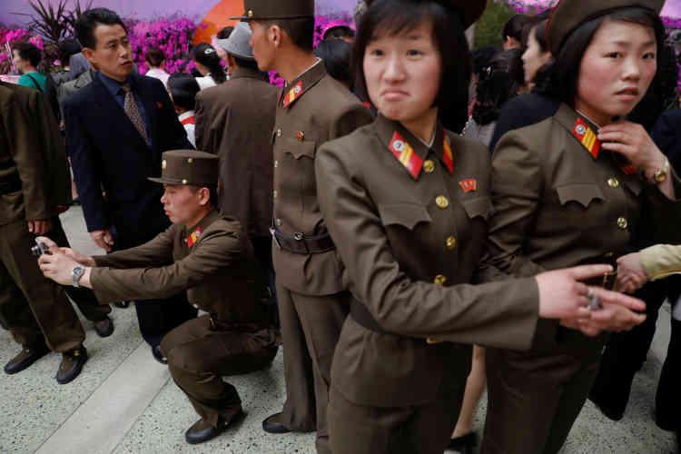 Des militaires posent dans l'exposition florale organisée à Pyongyang, le 16 avril.