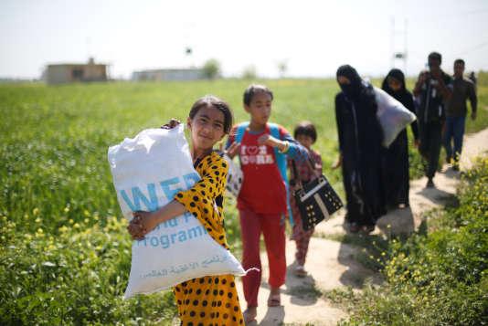 Des déplacés de Mossoul s'apprêtent à traverser le Tigre en bateau, à Thibaniya, au sud de Mossoul, le 16 avril.