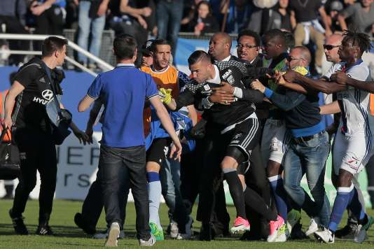 A security staff holds Lyon's goalkeeper Anthony Lopes (C) during scuffles at half-time between some of Lyon's players and Bastia supporters who invaded the pitch, during the French L1 football match Bastia (SCB) vs Lyon (OL) on April 16, 2017 in the Armand Cesari stadium in Bastia on the French Mediterranean island of Corsica.  Before the match, dozens of Bastia fans invaded the pitch at their Armand Cesari stadium and attacked Lyon players as they warmed up for a French Ligue 1 game. / AFP / PASCAL POCHARD-CASABIANCA / ALTERNATIVE CROP