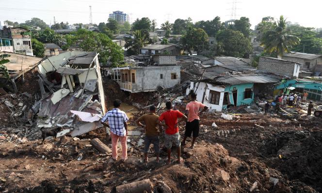 Des habitants du quartier devant les ruines du bidonville détruit par l'éboulement d'une pile d'ordures, à Meetotamulla, au Sri Lanka, le 16 avril.