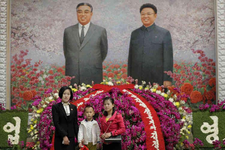 Une famille nord-coréenne pose devant un portrait de Kim Il-sung et Kim Jong-il.