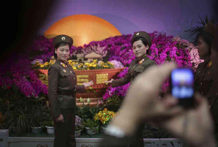 Dimanche 16 avril, deux militaires se font prendre en photo devant un parterre de fleurs à l'exposition floraleorganisée dans le cadre des fêtes du 105e anniversaire de la naissance de Kim Il-sung.