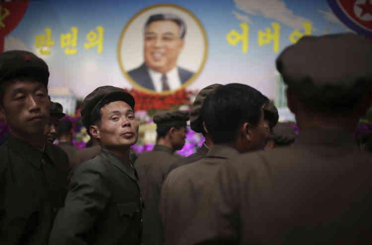 Des Nord-Coréens sous le portrait de Kim Il-sung, à Pyongyang.