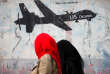 Deux femmes passent devant un graffiti contre les bombardements effectués au Yémen par les drones de l'armée américaine. A Sanaa, le 6 février.