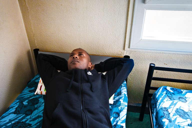 Merhawi dans l'une des deux chambres du centre de transit de Villeurbanne qu'il partageavec ses deux fils, Rafaël et Sem.