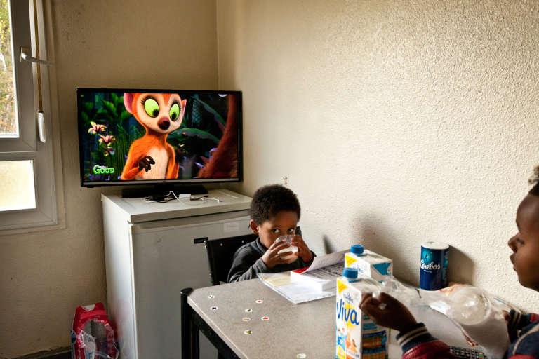 Sem, 4 ans, et Rafaël, 5 ans prennent leur goûter après l'école dans l'une des deux pièces de 7m2 du centre de transit de Villeurbanne où ils vivent avec leur père, Merhawi.