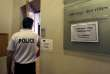 A police officer enters a court room in Marseille, France, Thursday, June 16, 2016. French authorities will deport 20 Russian men next week for their role in the violence that has marred the first week of the European Championship. (AP Photo/Claude Paris)