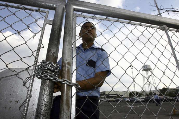 Un agent de sécurité derrière la grille de l'usine General Motors à Valencia au Venezuela, le 19 juin 2009. Le constructeur américain a annoncé le 20 avril 2017 l'arrêt de ses activités dans le pays après que les autorités ont saisi l'usine.