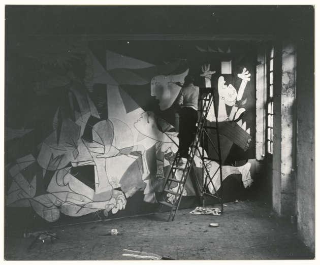 Pablo Picasso, photographié par Dora Maar,debout sur un escabeau peignant «Guernica», dans l'atelier de l'hôtel de Savoie, à Paris, en mai-juin 1937.