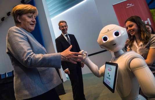 La chancelière allemande Angela Merkel avec un robot au stand digitalSTROM à la chancellerie à Berlin, le 26 avril 2017.