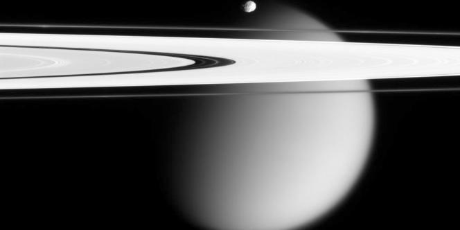 Sur cette image réaisée en 2006 par la sonde Cassini, on peut apercevoir la lune géante Titan et sa surface nébuleuse ainsi que sa (toute) petite soeur Epimetheus and smog-enshrouded Titan, with Saturn's A and F rings stretching across the frame.