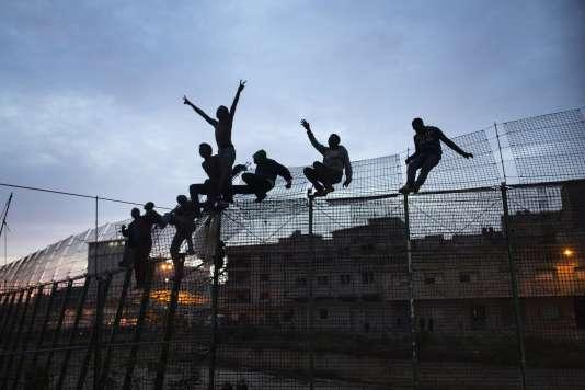 Des migrants d'Afrique subsaharienne escaladent un grillage métallique qui sépare le Maroc de l'enclave de Melilla, le 28 mars 2014.
