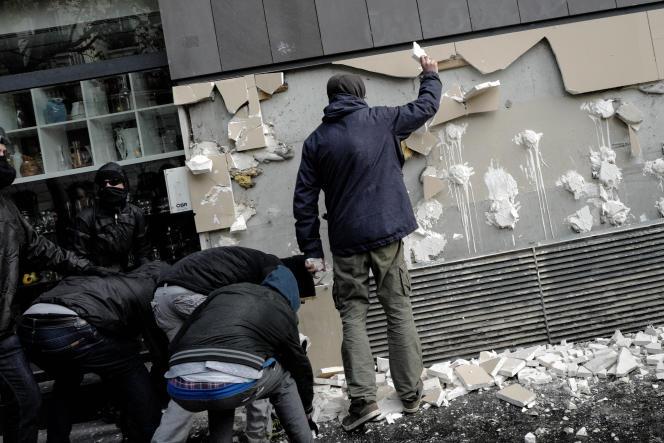 Des personnes appartenant à la mouvance 'anti-fasciste' cassent un mur pour en faire des projectiles et les lancer sur les forces de l'ordre, le 1er Mai, à Paris.