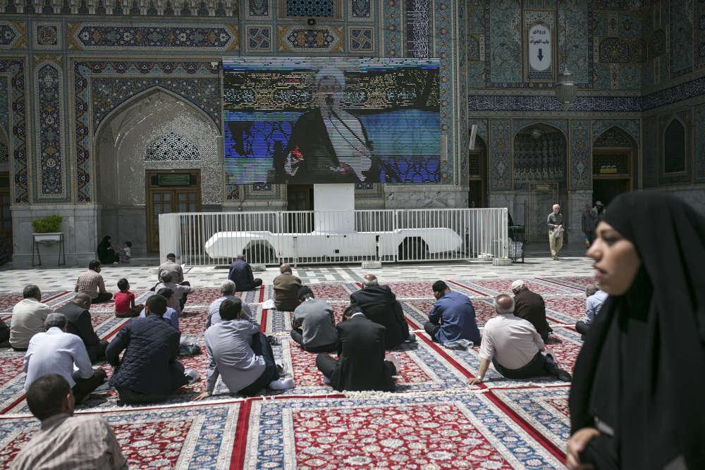 Des fidèles écoutent un prêche au mausolée de Reza.