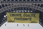 """Greenpeace activists display a banner at the Eiffel tower reads,""""liberty, equality, fraternity"""" in Paris, France, Friday, May 5, 2017. The protest is against far-right presidential candidate Marine Le Pen two days before the runoff. (AP Photo/Michel Euler)"""