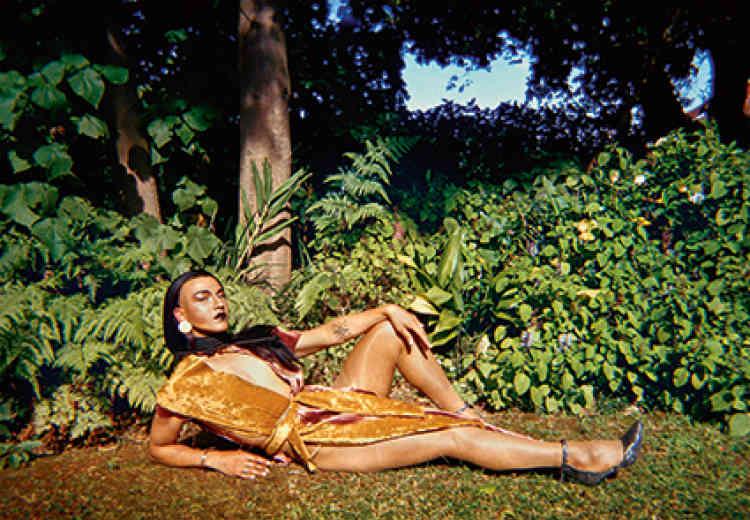 « Say her Name : Queezy », 2016. Photographie digitale sur polytwirl.Née en 1989 au Cap, Jody Brand est une photographe très tôt intéressée par les nouveaux médias. Elle documente la vie de la jeunesse multiculturelle du Cap. Dans la série de photographies grand format « Say her Name », elle crée un univers qui sublime le corps de femmes noires et de personnalités queer posant dans des lieux autrefois associés au colonialisme, un monde dont ils étaient exclus et qu'ils s'approprient avec outrance.
