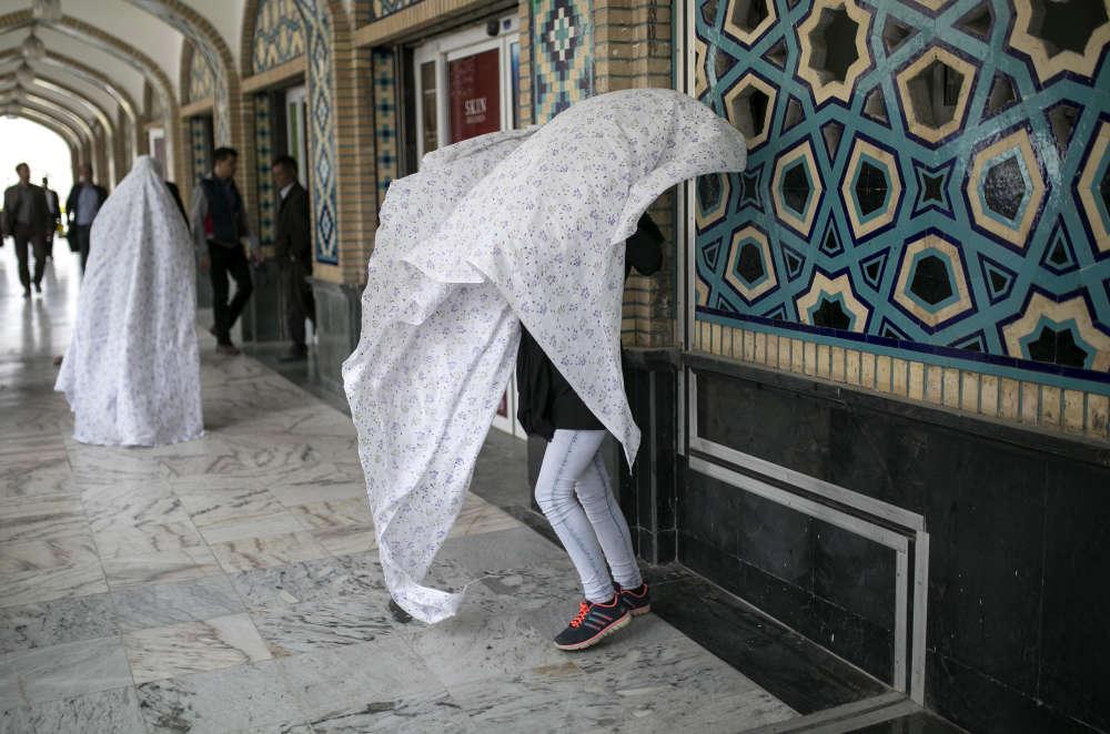 Une jeune femme ajuste son voile à l'entrée du mausolée Reza, puissante fondation que dirige Ebrahim Raisi, candidat à la présidence.