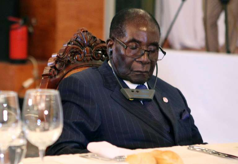 (FILES) This file photo taken on January 13, 2017 shows Zimbabwe President Robert Mugabe (R) attending a State Dinner for the Africa-France Summit with the Rwandan president in Bamako on January 13, 2017. Zimbabwean President Robert Mugabe, 93, is not asleep when he closes his eyes for long periods in public events but is resting his eyes from bright lights, his spokesman said on May 11, 2017. Mugabe has regularly had his eyes closed at recent appearances.  / AFP / SEBASTIEN RIEUSSEC