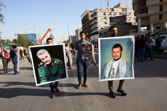 Le portrait du général Soleimani est brandi lors d'une manifestation, en mars 2015 à Bagdad, contre l'intervention militaire au Yémen de la coalition menée par l'Arabie saoudite. A droite, la photo du leader des rebelles houtistes, Abdel Malik Al-Houthi.