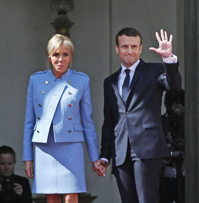 Emmanuel et Brigitte Macron, nouveau couple présidentiel, saluent François Hollande après la cérémonie de passation de pouvoirs, le 14 mai2017.