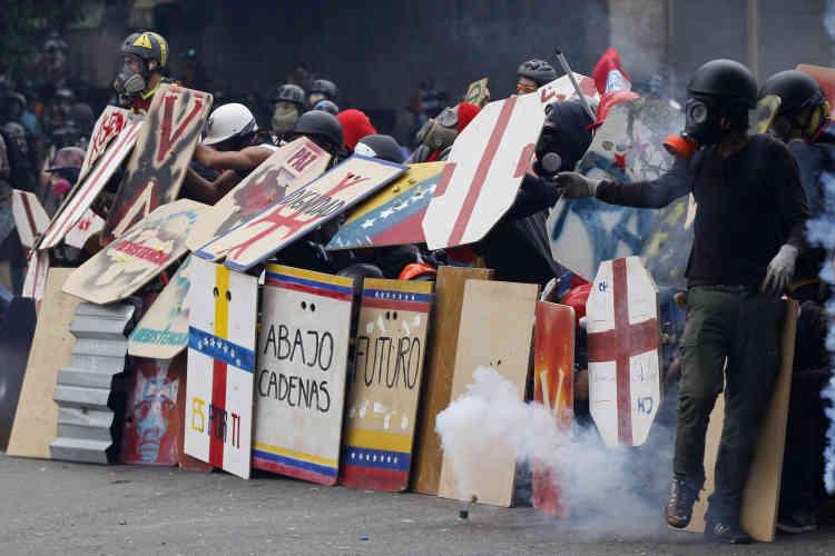 Des manifestants font face aux forces de sécurité bloquant une marche d'étudiants vers le ministère de l'éducation à Caracas, le 8 mai.