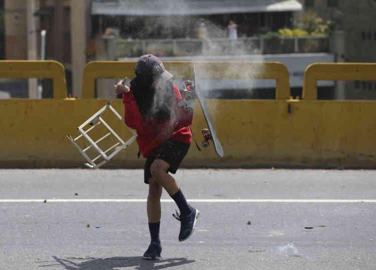 Une manifestante anti-gouvernement dévie l'impact d'une cartouche de gaz lacrymogène avec sa planche de skate à Caracas, le 6 avril.