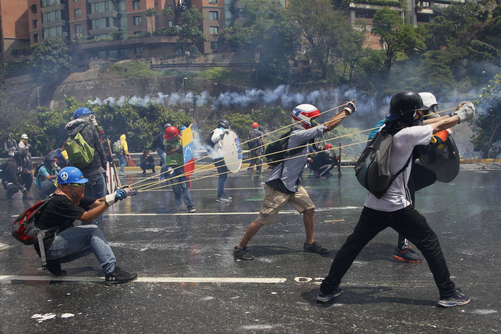 Caracas, le 10 mai. Des manifestants se préparent à lancer sur les forces de l'ordre une bouteille de verre remplie de matières fécales et d'eau («puputov»), sur certaines figurent des messages : « Pour les prisonniers politiques !» ou encore « Envoyé avec amour».