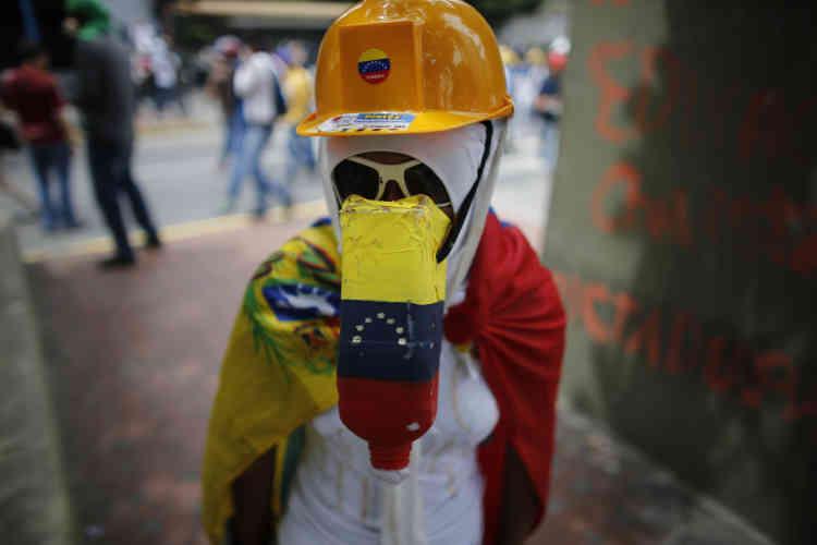 Une manifestante équipée d'un casque de chantier, de lunettes de soleil et d'une bouteille plastique remplie de boules de coton faisant office de masque à gaz, à Caracas, le 8 mai.