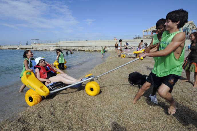 Le service civique fait partie des engagements reconnus par le décret du 11mai. Ici, desjeunes volontaires en service civique aident une femme handicapée à prendre un bain de mer, en 2010, à Marseille.