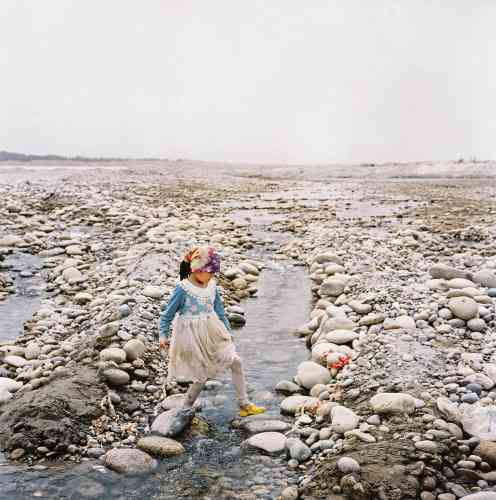 En haut à droite, une petite fille court sur le fleuve Yurungkash, dit aussi « fleuve de jade blanc », pour les pierres qu'on y trouve.
