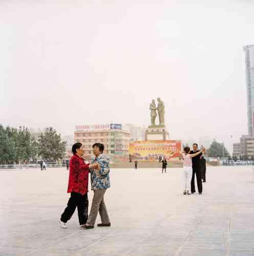 Sur la place de l'Unité, au cœur de Hotan, Chinois han et Ouïgours dansent séparément. En arrière-plan, une statue d'Oncle Kurban, un Ouïgour exprimant sa gratitude à Mao. Omniprésentes sur la place, hors champ, des forces de sécurité.