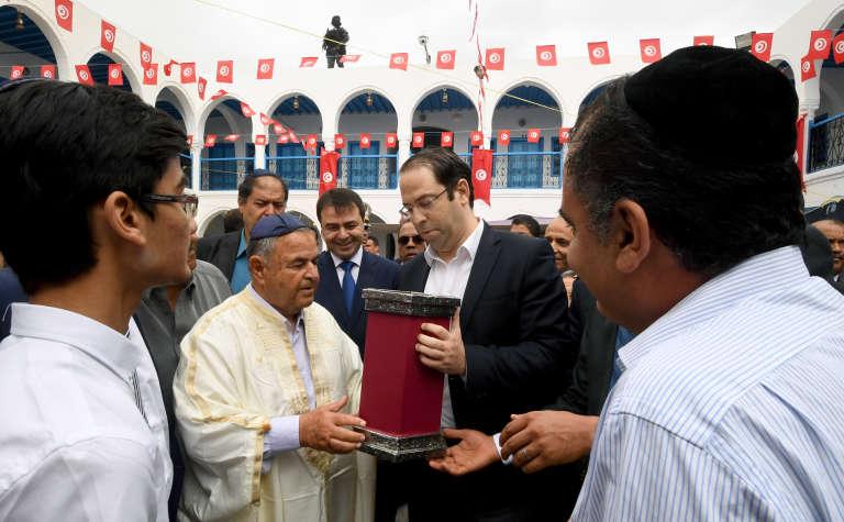 Le premier ministre Youssef Chahed reçoit un cadeau de la communauté juive de Djerba, lors du pèlerinage de la Ghriba, la synagogue de l'île tunisienne, le 14 mai 2017.