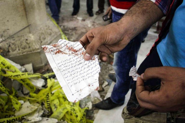 Un Egyptien montre une page de l'évangile de Jean ensanglantée par l'attentat perpétré contre les chrétiens coptes de l'église de Tanta, au nord du Caire, le 9 avril 2017.