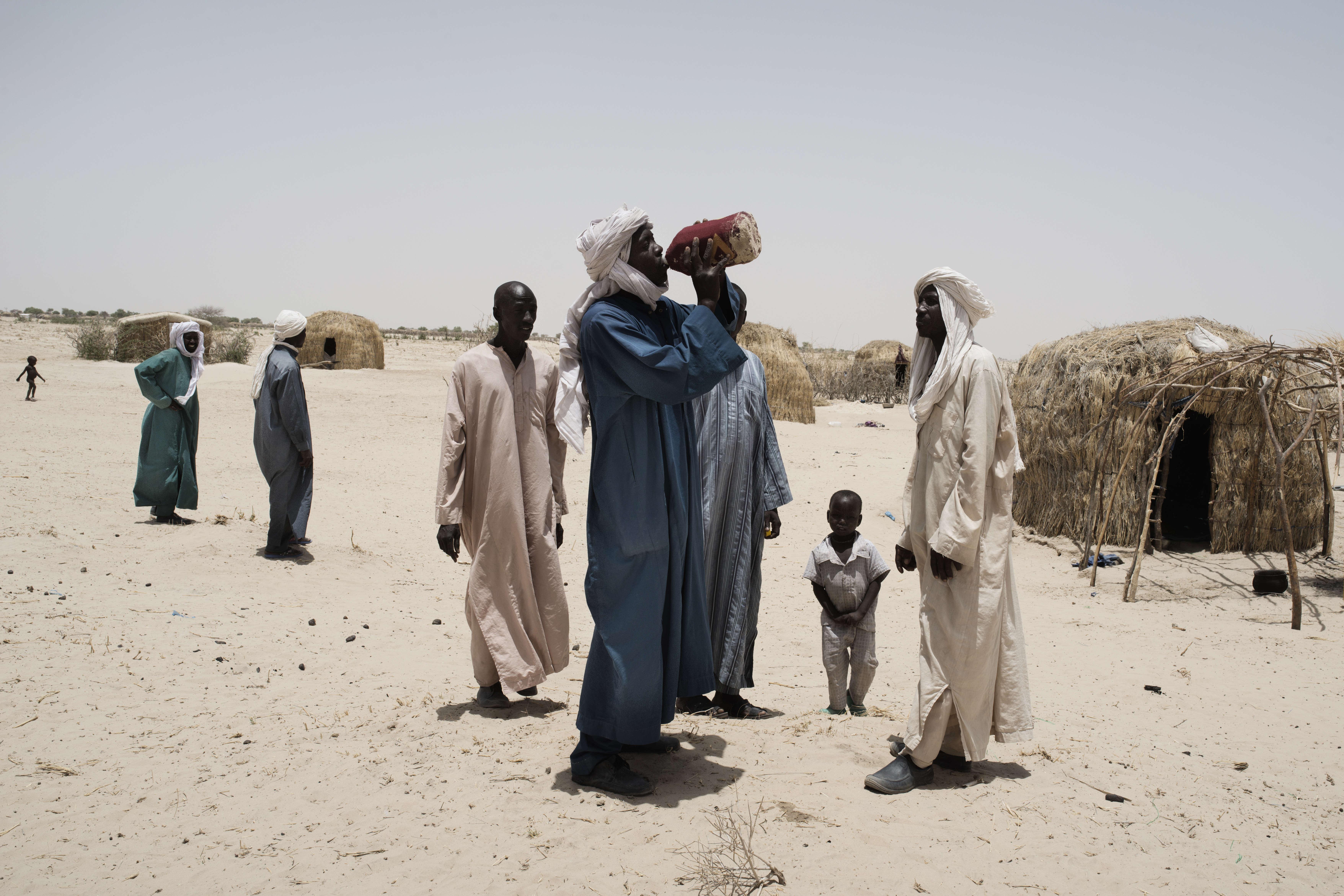 Dans le camp de déplacés de Amma, aménagé par l'ONG Care, des hommes se désaltérent. Le mois de mai est le plus chaud de l'année. Il fait plus de 40 degrés.