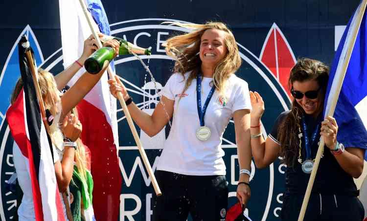 La Costaricaine Leilani McGonagle (bronze) et la Française Johanne Defay (à droite) célèbrent la victoire de Pauline Ado aux championnats du monde des nations de surf.