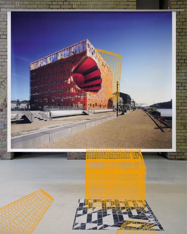 Pour leur exposition à la galerie berlinoise Aedes, les architectes Dominique Jakob et Brendan MacFarlane ont juxtaposé des maquettes de leurs constructions aux photos des sites (ici, le Cube Orange de Lyon, 2010).