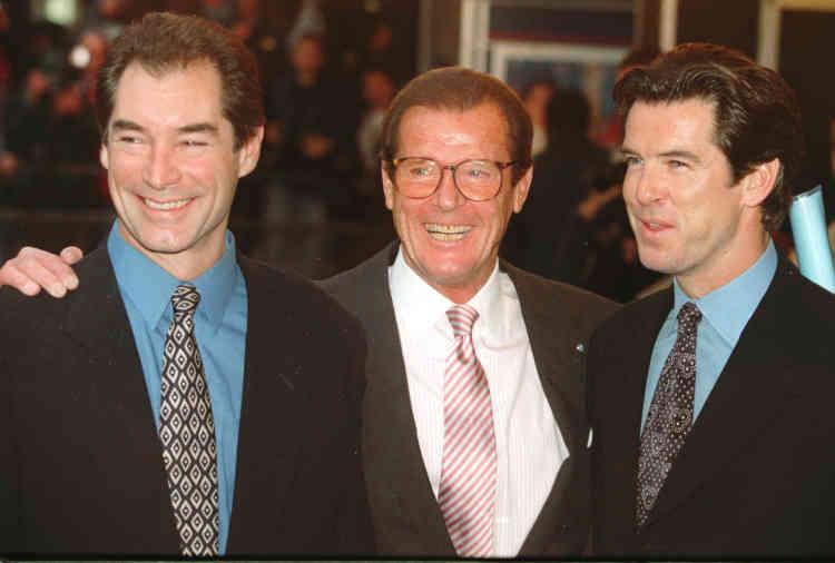 Roger Moore au centre et les deux acteurs qui lui ont succédé dans le rôle de l'agent secret britannique. Timothy Dalton à gauche, et Pierce Brosnan à droite, le 17novembre 1996.C'est pour sa mission humanitaire, et non pour sa carrière d'acteur, que Roger Moore avait été anobli par la reine Elizabeth II en 2003.