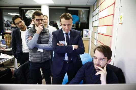 Emmanuel Macron, Ismaël Emelien, Mounir Mahjoubi et le graphiste Thibault Caizergues regardent le nouveau site Internet d'En Marche!,à Paris, le 2 février.