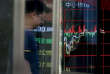 A man is reflected on a glass panel as he walks past an electronic board displaying stock trading index at a brokerage house in Beijing, Wednesday, May 24, 2017. Chinese stocks sank Wednesday after Moody's cut Beijing's government debt rating and other Asian markets rose following Wall Street's advance. (AP Photo/Andy Wong)