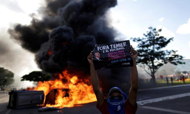 Un manifestant brandit une affiche« Temer dehors» près d'une barricade en feu, à Brasilia le 24 mai.