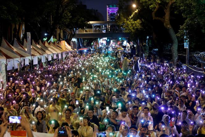 Des militants LGBT montrent leur joie en agitant leur téléphone portable aux couleurs de l'arc-en-ciel à Taipei, le 24 mai.