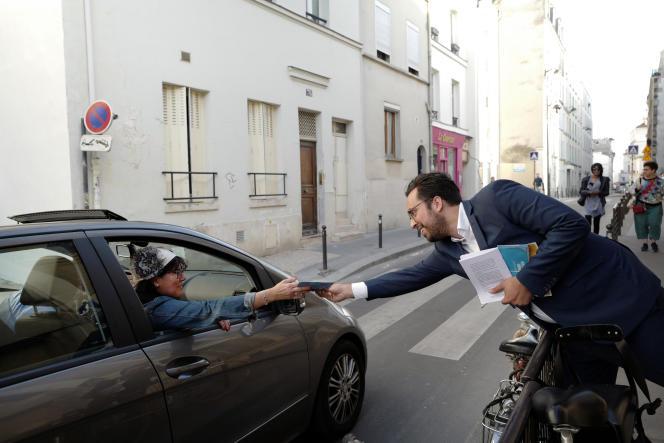 Le nouveau secrétaire d'Etat chargé du numérique, Mounir Mahjoubi, donne un tract à une habitante du 19e arrondissement de Paris, le 24 mai.
