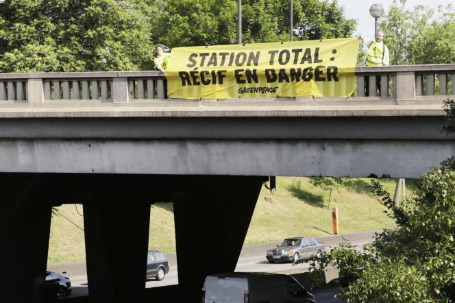 Occupation brève de stations-service Total, banderole sur le boulevard périphérique parisien, samedi 27 mai, Greenpeace et ANV-COP21 ont agi contre les projets pétroliers de Total au large des côtes brésiliennes.