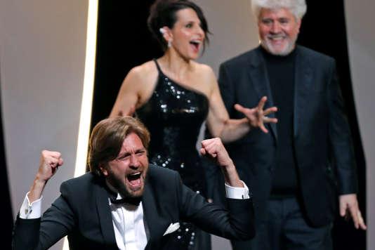 Le réalisateur suédois Ruben Östlund, Palme d'or 2017 pour« The Square», avec l'actrice Juliette Binoche et le cinéaste Pedro Almodovar, lors de la cérémonie de clôture du 70e Festival de Cannes, le 28mai 2017.