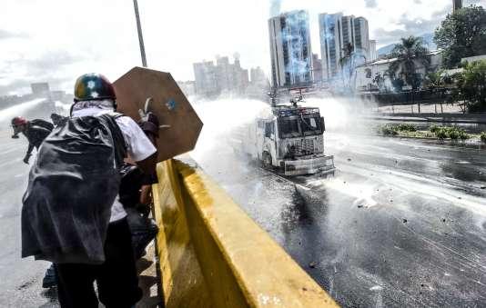 Un affrontement au jet d'eau entre des manifestants et la police, à Caracas, lundi 29 mai.